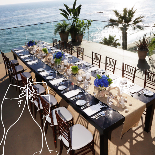 Large table is set for an event overlooking the ocean.